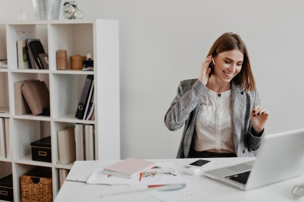 Słodka krótkowłosa biznesowa dama śmieje się słuchając muzyki na słuchawkach. portret kobiety w biurze ubrania siedzi w miejscu pracy.