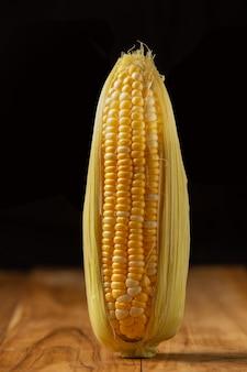 Słodka kukurydza umieszczona na drewnianej podłodze.