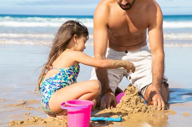 Słodka mała dziewczynka i jej tata budują zamek z piasku na plaży, siedząc na mokrym piasku, ciesząc się wakacjami na morzu