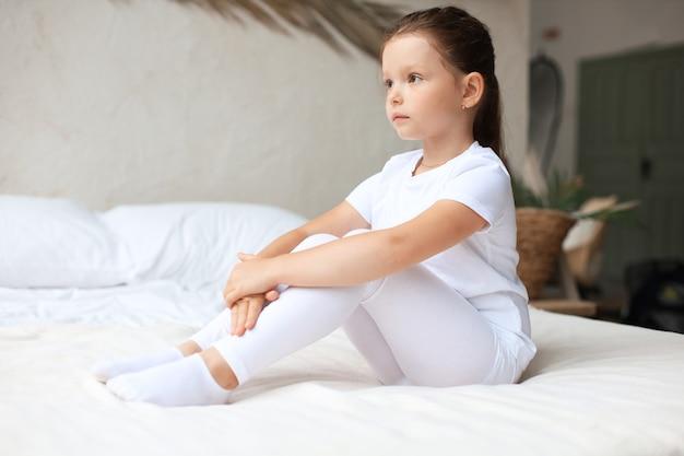 Słodka mała dziewczynka siedzi na łóżku w domu.