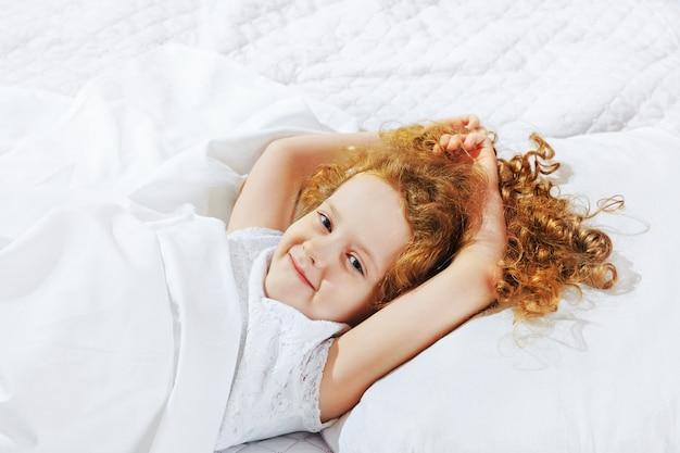 Słodka mała dziewczynka śpi w łóżku.