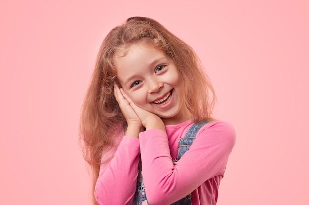 Słodka mała dziewczynka uśmiecha się radośnie i trzyma splecione dłonie pod policzkiem, stojąc na różowym tle i patrząc na kamery