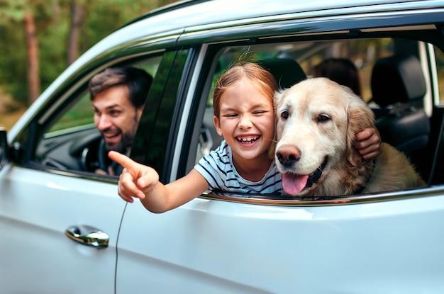Słodka mała dziewczynka wraz ze swoim przyjacielem psem labradorem i rodzicami wychodzą na weekend radośnie wyglądając przez okno samochodu. wypoczynek, podróże, turystyka.