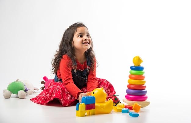 Słodka mała indyjska azjatka bawiąca się kolorowymi klockami na białym tle