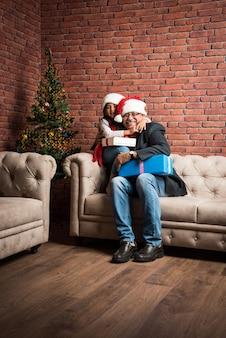Słodka mała indyjska azjatka i dziadek świętują boże narodzenie, siedząc nad sofą z prezentami i choinką w domu