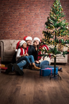 Słodka mała indyjska azjatka świętująca boże narodzenie z dziadkami i choinką siedzącą na kanapie, w kapeluszu świętego mikołaja i z mnóstwem prezentów