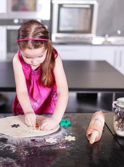Słodka mała śliczna dziewczyna uczy się robić ciasto w nowoczesnej kuchni domowej