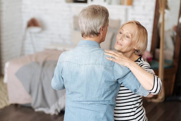 Słodka melodia emocji. pełen wdzięku kochająca starsza pani tańczy ze swoim mężczyzną i wygląda marzycielsko, jednocześnie ciesząc się swoim czasem z nim