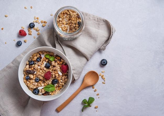 Słodka muesli z malinami, jagodami i mlekiem kokosowym w biały talerz na jasnoszarym stole. energia i wegańskie śniadanie. widok z góry i kopiowanie miejsca.