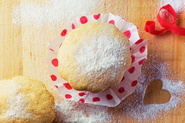Słodka muffinka z cukrem i dekoracją z czerwonej wstążki