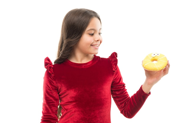 Słodka obsesja. szczęśliwe dzieciństwo i słodkie smakołyki. łamanie koncepcji diety. dziewczyna trzymać słodki pączek białe tło. dziecko głodne słodkiego pączka. poziom cukru i zdrowe odżywianie. porady dietetyka.