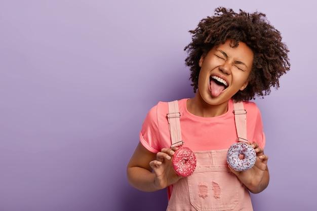 Słodka obsesja. zabawna kobieta z kręconymi włosami wystawia język, trzyma dwa pyszne pączki, nosi różowe ubrania, odizolowane na fioletowej ścianie studia