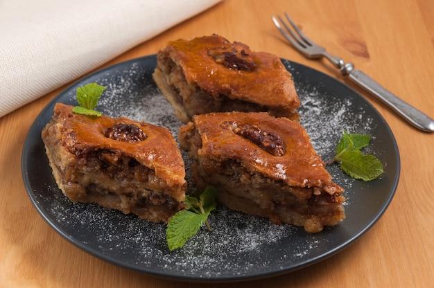 Słodka orientalna baklava deserowa z orzechami na ciemnym talerzu