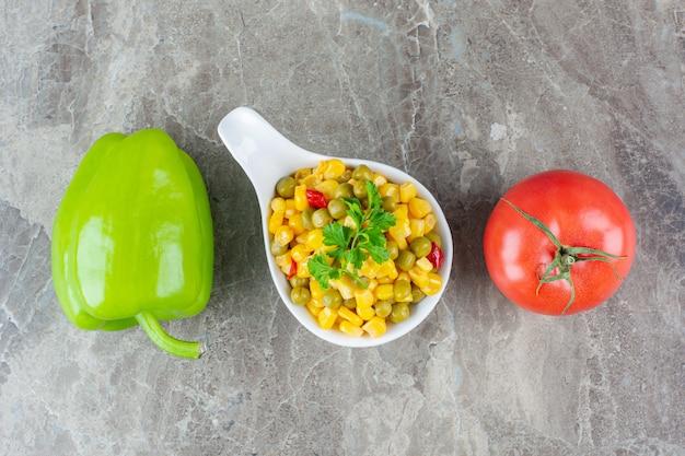 Słodka papryka i pomidory obok sałatki kukurydzianej w łyżce, na marmurowej powierzchni.