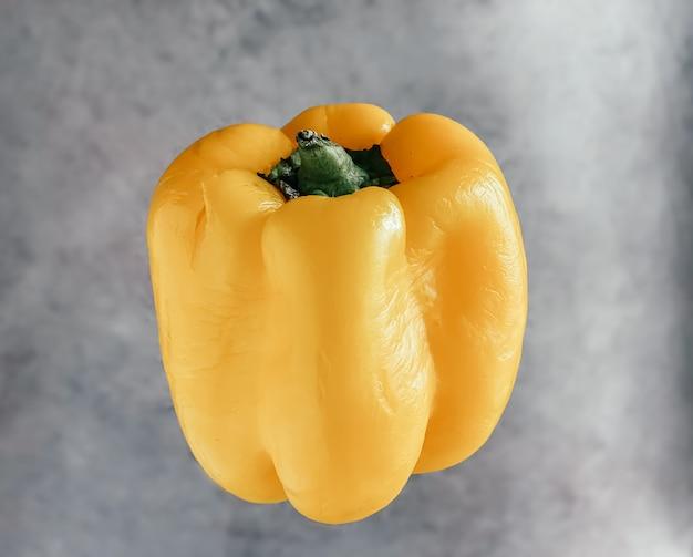 Słodka papryka lewitująca w powietrzu na szarym marmurowym tle. koncepcja zdrowej żywności i stylu życia.