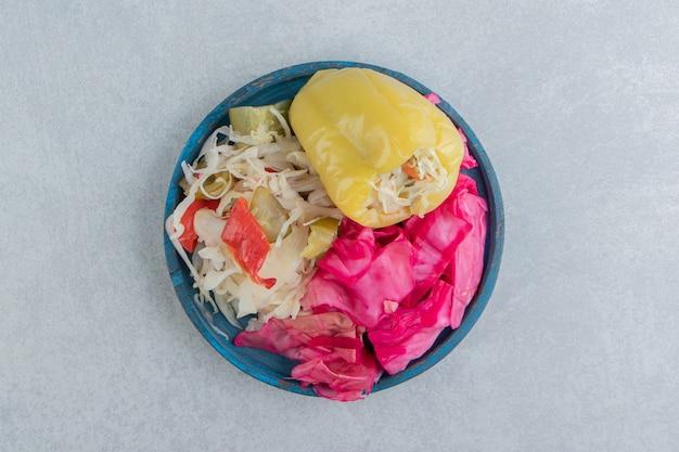 Słodka papryka, posiekana zielona i czerwona kapusta kiszona w misce
