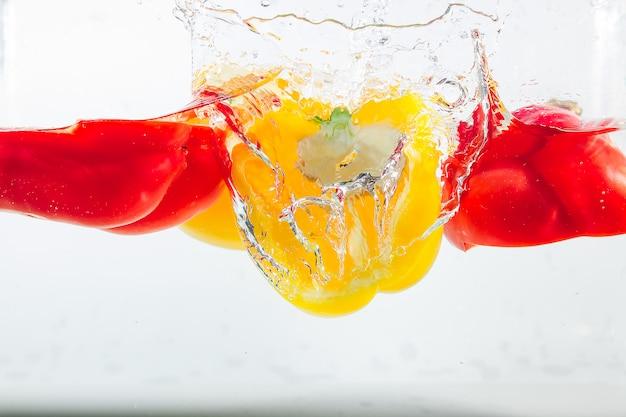 Słodka papryka w żółtych, czerwonych, zielonych plamach wody, słodka papryka na białym tle
