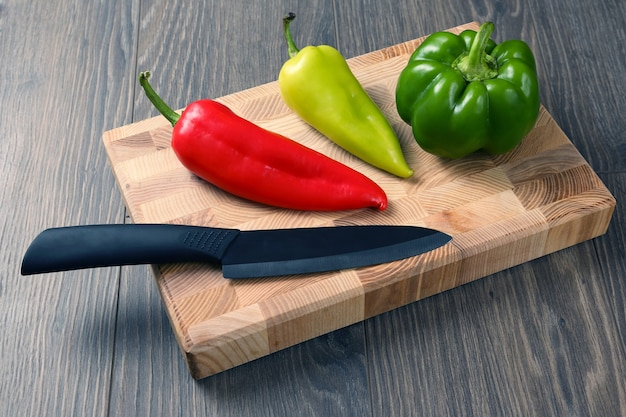 Słodka papryka z ceramicznym nożem na drewnianej desce