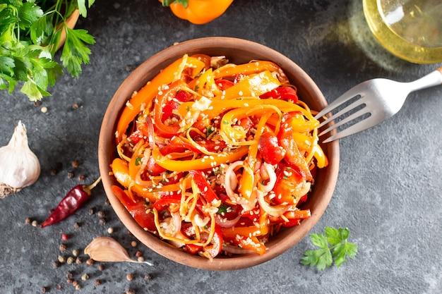 Słodka papryka z marchewką, sezamem i warzywami w misce na ciemnym tle. pikantne zdrowe jedzenie. widok z góry