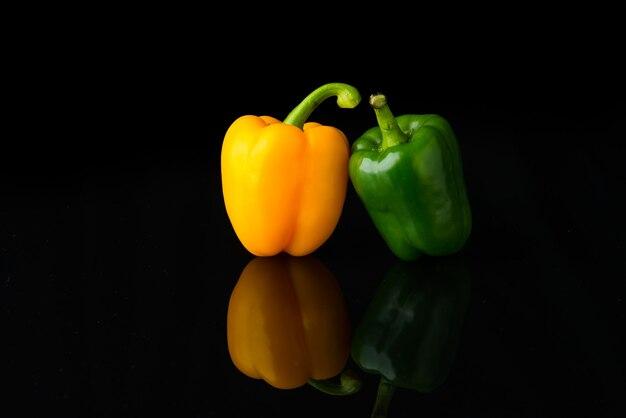 Słodka papryka żółta i zielona na białym tle na czarnym tle