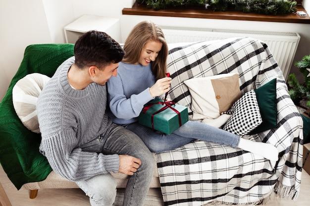 Słodka para otwierająca świąteczne prezenty w salonie w domu