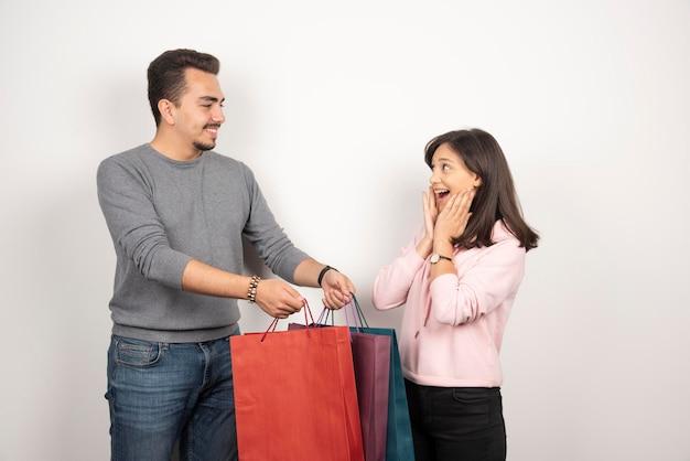 Słodka para przewożących torby na zakupy na białym tle.