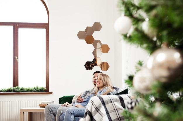 Słodka para przytula się na kanapie w domu podczas świąt