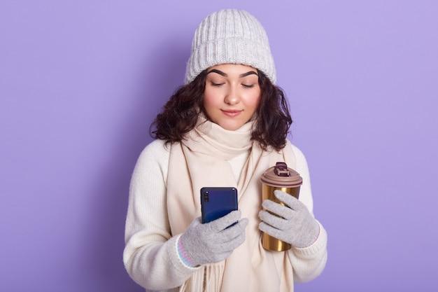 Słodka piękna czarnowłosa młoda kobieta trzyma termicznego kubek