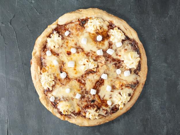 Słodka pizza z pastą czekoladową nutella, banan, serek, ser mozzarella, sulguni, pianki. szeroki bok. widok z góry. na szarym tle betonu. odosobniony.