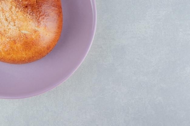 Słodka pojedyncza bułka na fioletowym talerzu.