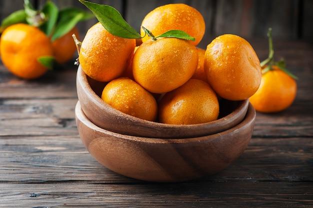 Słodka pomarańczowa mandarynka na drewnianym stole, selektywna ostrość