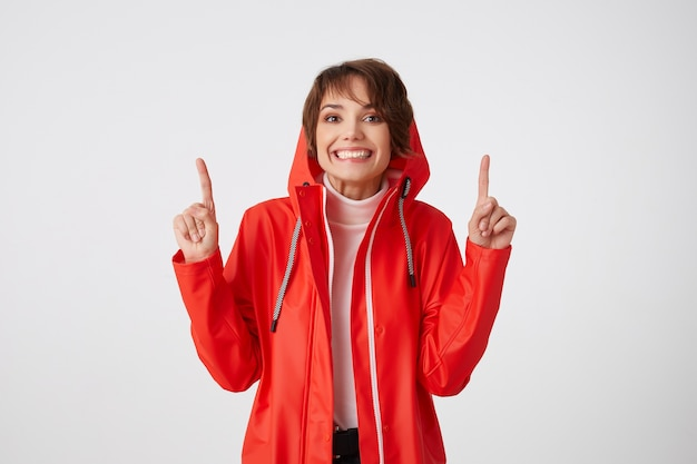 Słodka pozytywna krótkowłosa dziewczyna w czerwonym płaszczu przeciwdeszczowym, szeroko się uśmiecha, patrzy, chce zwrócić twoją uwagę na przestrzeń nad jej głową, wskazuje palcami w górę. na stojąco.