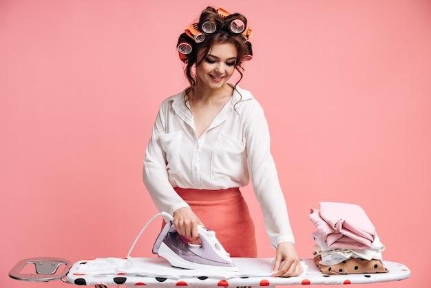 Słodka, pracowita gospodyni prasuje na desce do prasowania górę ubrań