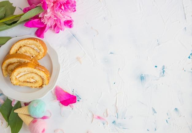 Słodka rolka na drewnianym tle. deser na śniadanie z kwiatami. romantyczne śniadanie