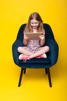 Słodka ruda dziewczyna jest uzależniona od tabletu siedzącego na krześle i używającego go na żółtej ścianie studia