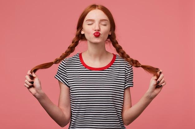 Słodka rudowłosa dziewczyna z czerwonymi ustami wysyła pocałunek z zamkniętymi oczami trzymając dwa warkocze w rękach ubrana w t-shirt w paski, flirtuje na białym tle