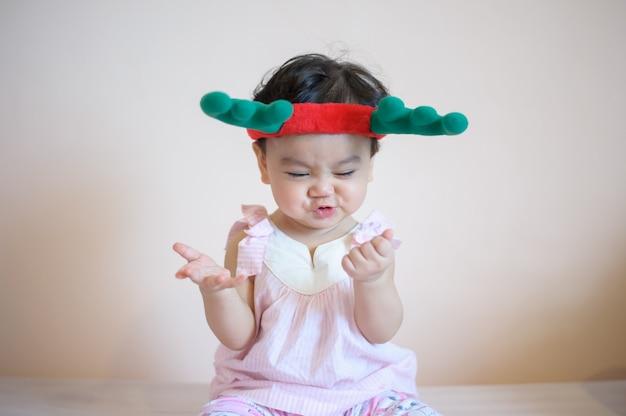 Słodka, szczęśliwa mała azjatka, która właśnie miała zęby dziecka, robi zabawną pozę. nosi kapelusz z poroża i patrzeć na aparat na białym tle. koncepcja ekspresji dziecka