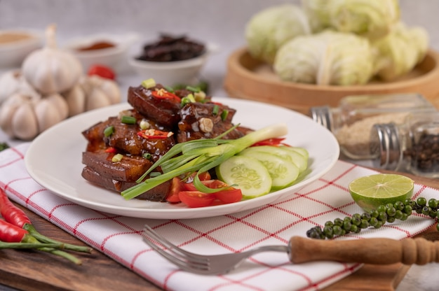 Słodka wieprzowina na białym talerzu z posiekaną cebulką, chili, limonką, ogórkiem, pomidorem i czosnkiem.