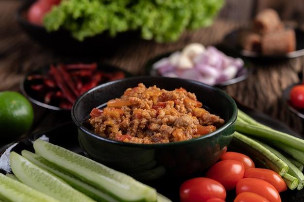 Słodka wieprzowina w czarnej misce z ogórkami, długą fasolą, pomidorami i dodatkami