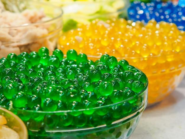 Słodka zielona żelkowa bańka w szklanej misce. zielona kula tapioki lub boba. tajski deser (ruam mit)