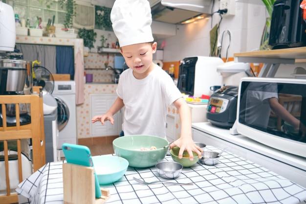 Słodki azjatycki chłopiec bawiący się w gotowanie śniadania, młody bloger robi vloga na kanale mediów społecznościowych