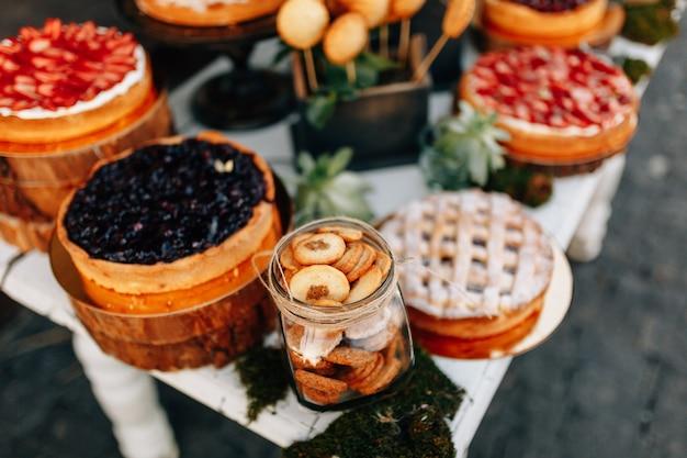 Słodki bar weselny jesienią. ciasto, babeczki, słodycz i kwiaty.