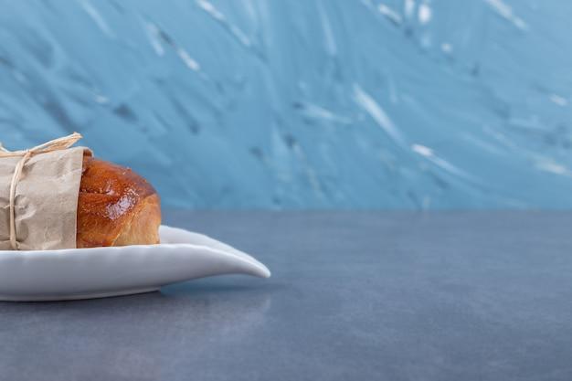 Słodki bochenek na talerzu na marmurowym stole.
