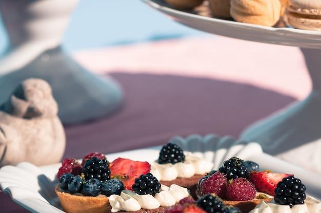 Słodki bufet z babeczkami jagody makaroniki desery dekoracja stołu weselnego lub okolicznościowego