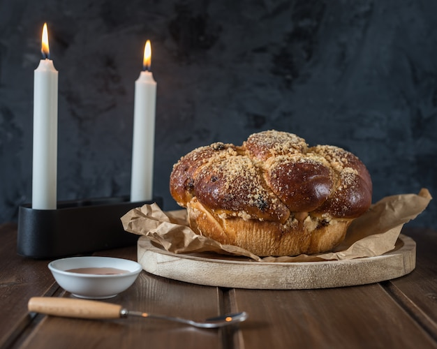 Słodki chleb challah na zalesionym okrągłym talerzu na drewnianym brązowym stole z miodem i dwiema świeczkami w wieczór szabatowy, dzięki czemu kidush