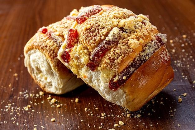 Słodki chleb z dżemem z guawy i słodką mąką na brązowym drewnianym stole. jest to rodzaj chleba powszechnego w brazylii i portugalii, wyrabiany ze słodkiego ciasta.