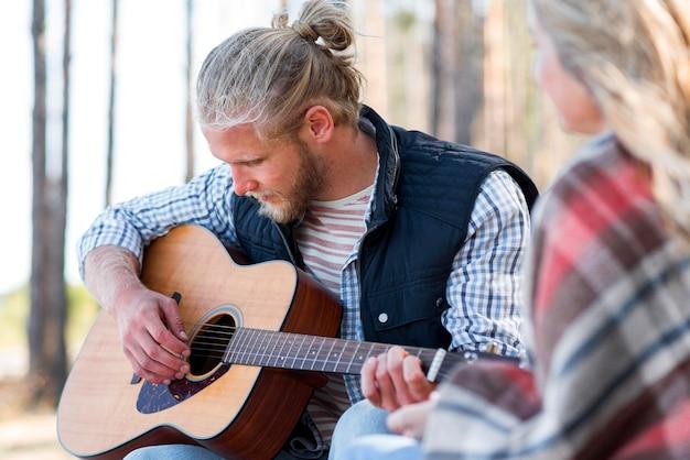 Słodki chłopak gra na gitarze akustycznej