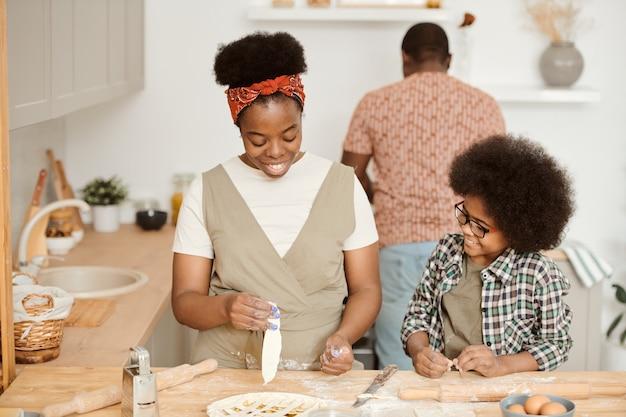 Słodki chłopak pomaga mamie z domowym ciastem w kuchni
