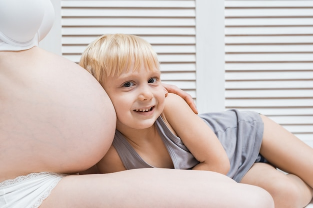 Słodki chłopczyk oparł ucho na brzuchu ciężarnej mamy. młoda kobieta w ciąży i najstarszy syn