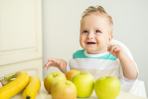 Słodki chłopczyk siedzi przy stole w foteliku dla dziecka je jabłko w białej kuchni